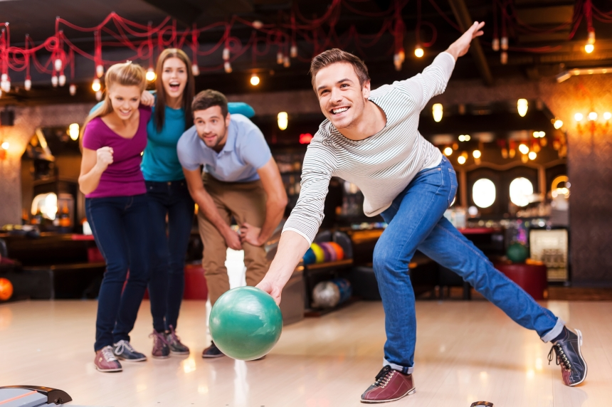 He is a winner. Handsome young men throwing a bowling ball while three people cheering